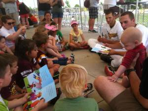 The Willmar Stingers read to the kids before the baseball game. All the kids got free books to bring home too.